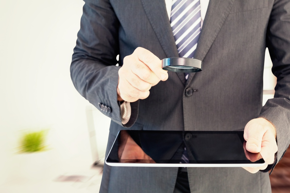 Businessman looking at tablet with magnifying glass against laptop on desk with glasses and notepad.jpeg